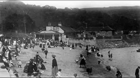 Black and white photo of The Beach House and the beach, showing people in Victorian dress.