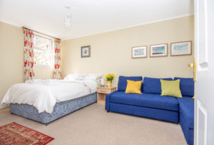 Bedroom with double bed and corner sofa bed